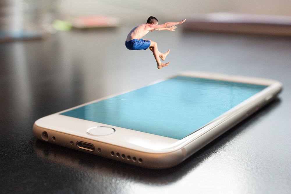 Fotomontage eines Menschen, der in ein iPad springt, auf dessen Oberfläche Wasser dargestellt ist.