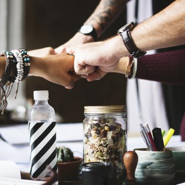 Projektmanagement in der tubCloud - das Kollaborationswerkzeug Deck entdecken. Die Fotografie zeigt zur Illustration von Empowerment einen Kreis aus Menschen, die sich in der Mitte per Faust berühren und Teamarbeit signalisieren.