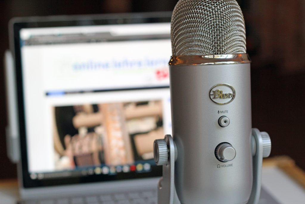 Fotografie eines Mikrofons, im Bildhintergrund ein Notebook