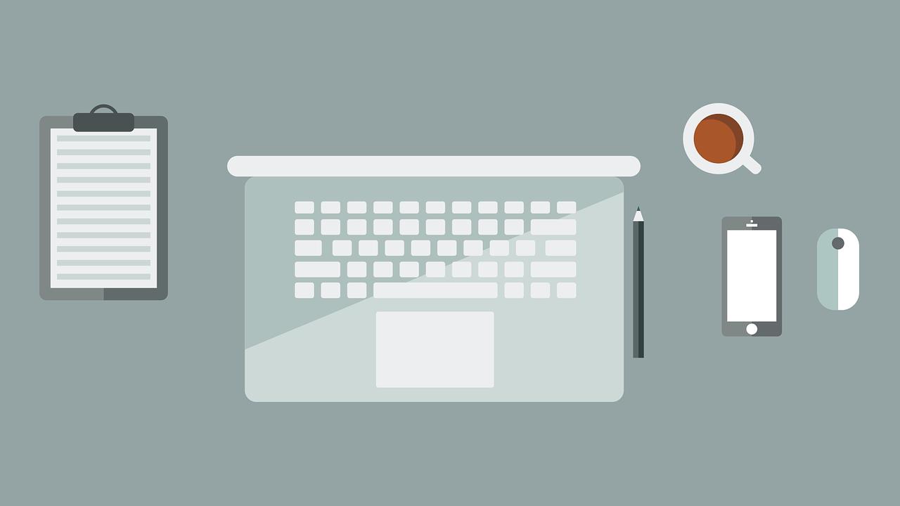 Vogelperspektive auf einen Computer, daneben eine Tasse Kaffee, ein iPhone, Bleistift und ein Notizblock